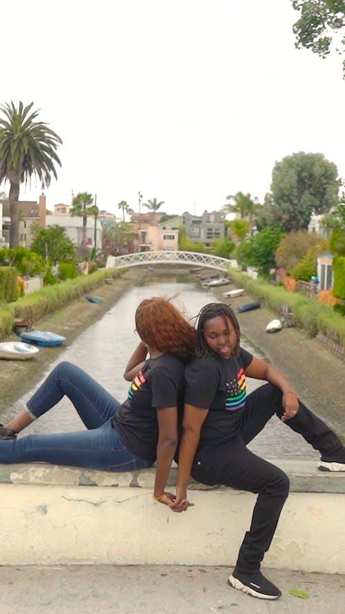 Two Women Sitting Back To Back Over The Bridge Ledge