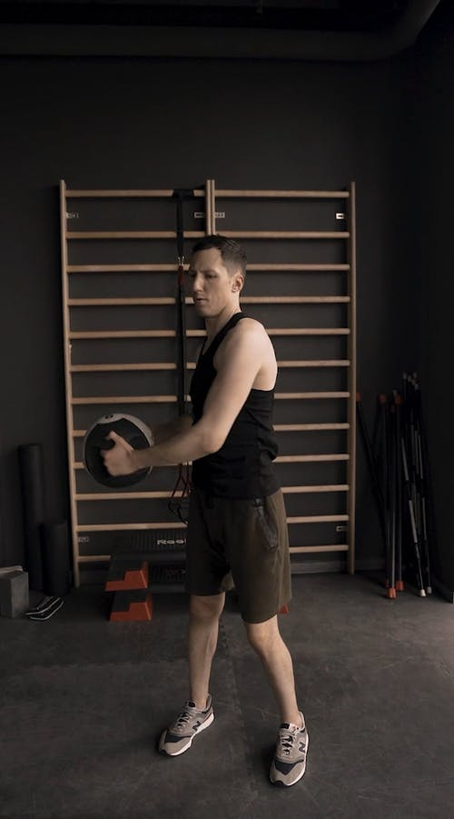 A Man Lifting A Kettle Bell Around His Body