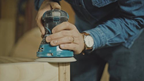A Person Using a Grinding Machine to Smoothen the Wooden Surface