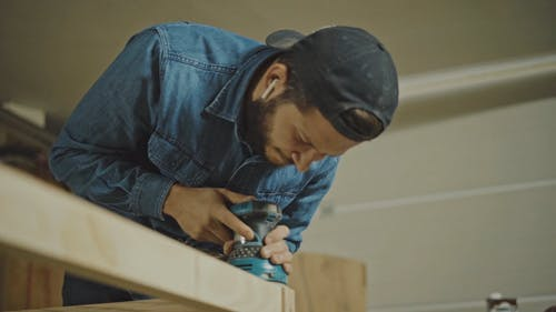 A Joiner Using a Grinding Machine to Smoothen the Wooden Surface