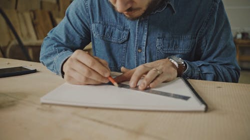 A Man Drawing a Plan on a Sketchpad