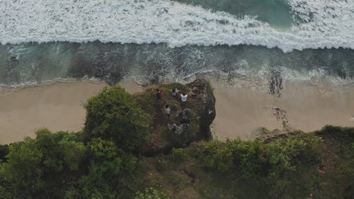 People Chilling at the Edge of a Cliff by the Beach