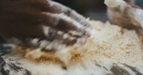 Close-Up View of a Person Mixing a Flour