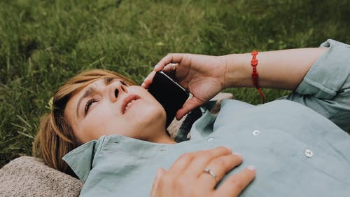 Woman Lying Down on Grass while Talking on the Phone