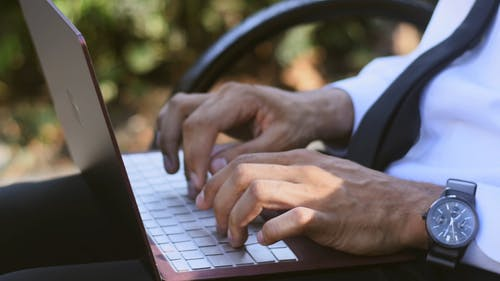 A Person Typing On A Laptop Keyboard