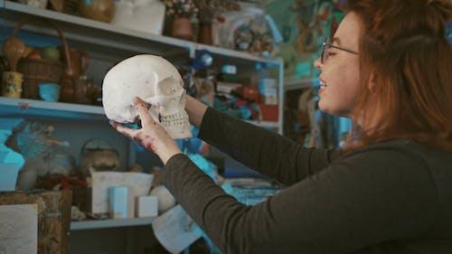 A Woman Holding a Skull Plaster Sculpture