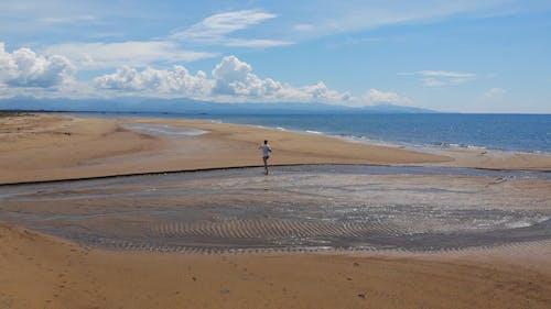 Man Running On A Sandy Beach Shore