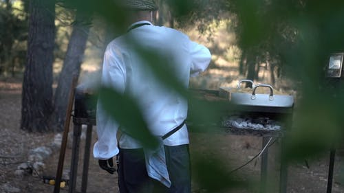 Person Grilling a Sausages and Meat on the Outdoors