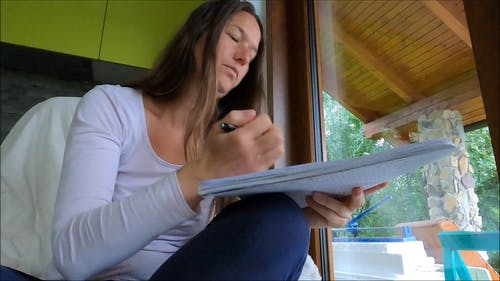 Woman in White Sweater Writing in a Notebook