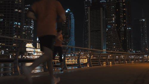 People Jogging at Night on Bridge