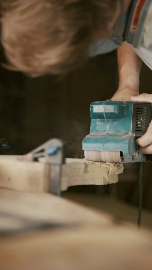 Person Sanding a Wood