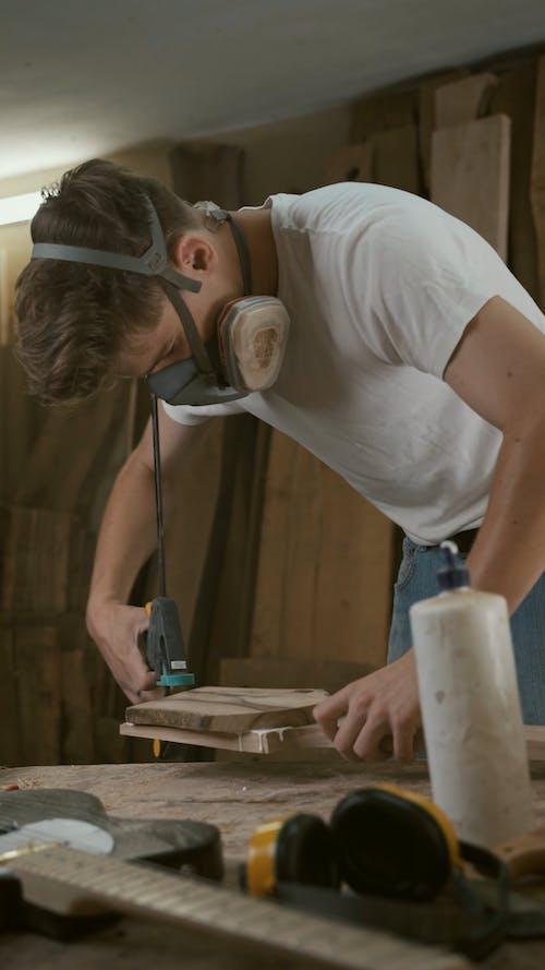 Guy Fixing Wood to make Guitar
