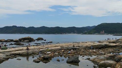 Tourists by the Rocky Coastal Beach