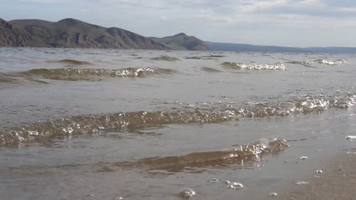 Bubbly Ocean Waves Coming to the Beach Coast