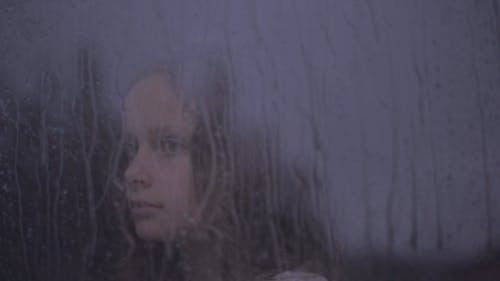 Woman Looking outside of a Window on a Rainy Day