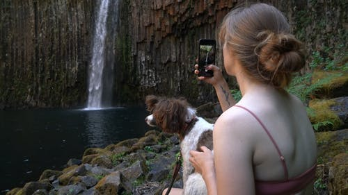 Woman with Her Dog Taking Picture of a Waterfall