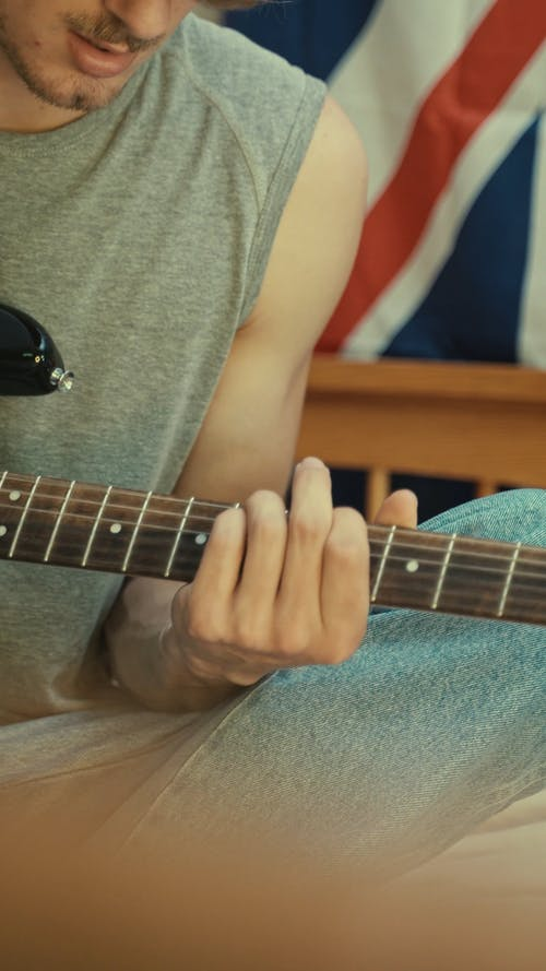 Teenager Boy Playing Guitar on Bed