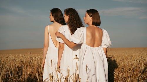 Women in White Dresses Standing in Wheat Field