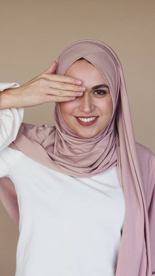 Woman in Hijab Smiling While Covering Her Eyes With Her Hands