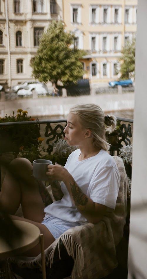 A Woman Having Coffee On A Veranda