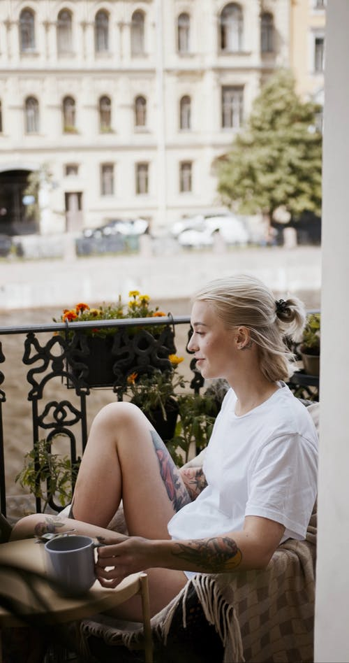 A Woman Drinking Her Coffee In The Balcony