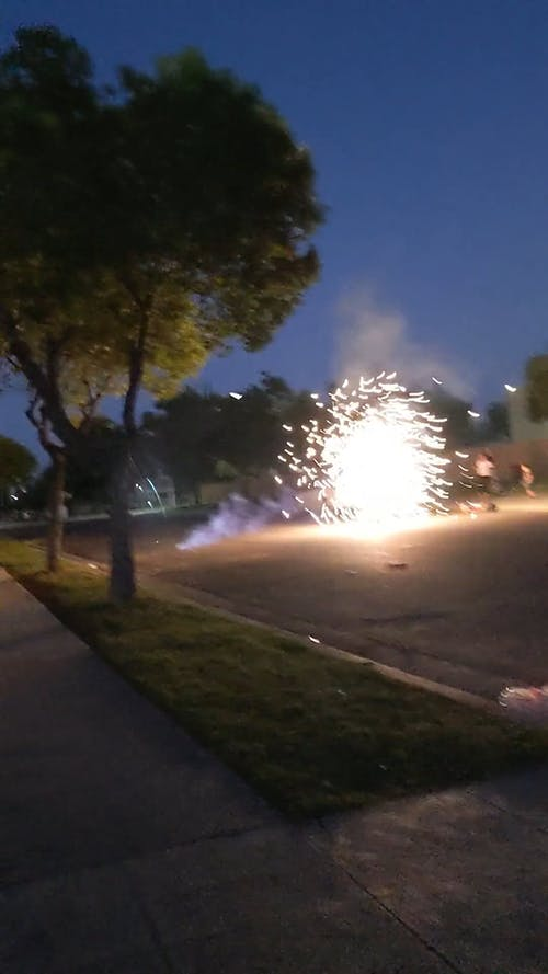 People Watching a Lighted Firecrackers on Street