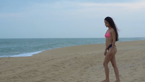 Woman in Bikini Walking and Spinning on Beach Shore