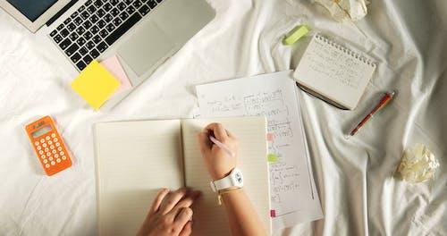 Persona Escribiendo En El Cuaderno Mientras Está En La Cama