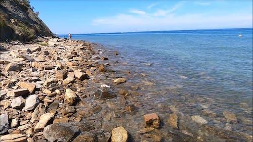 Man Walking on Rocky Seashore