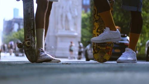 Men Standing On The Sidewalk Holding Skateboard