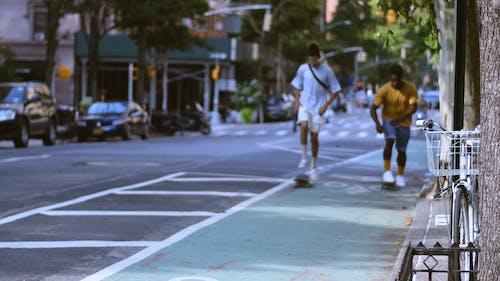 Two Young Men Skateboarding On The Street Sidewalk