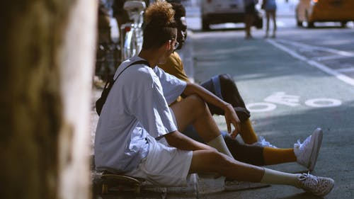 Двое мужчин сидят на тротуаре и разговаривают друг с другом