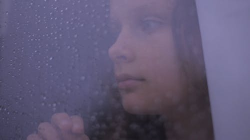 A Young Girl Looking Outside The Window Glass