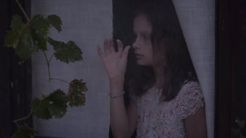 Young Girl Looking at Rain through a Glass Window
