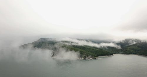 Thick Fog Partially Covering The Mountain Landscape
