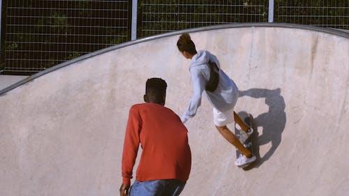 Two Skateboarders Using The Skate Park Ramp