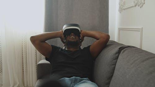 Guy wearing VR Headset Looking around his Room