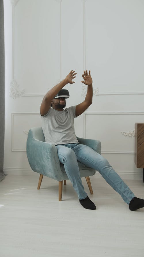 Man Sitting on Chair Feeling the Experience of VR Headset
