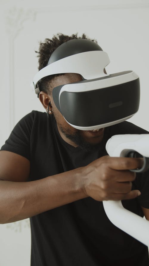 Guy Playing Shooting Game wearing a VR Headset