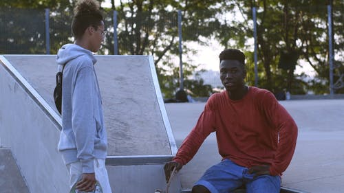 Two Young Guys Discussing about Skateboard Tricks