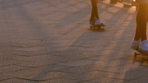Two Skateboarders Rolling through Pavement