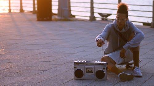 Two Skateboarders Sitting on Promenade Enjoying Boombox Music