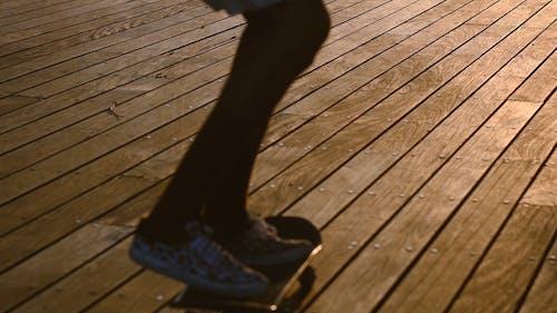 Skateboarding Over The Wooden Boardwalk