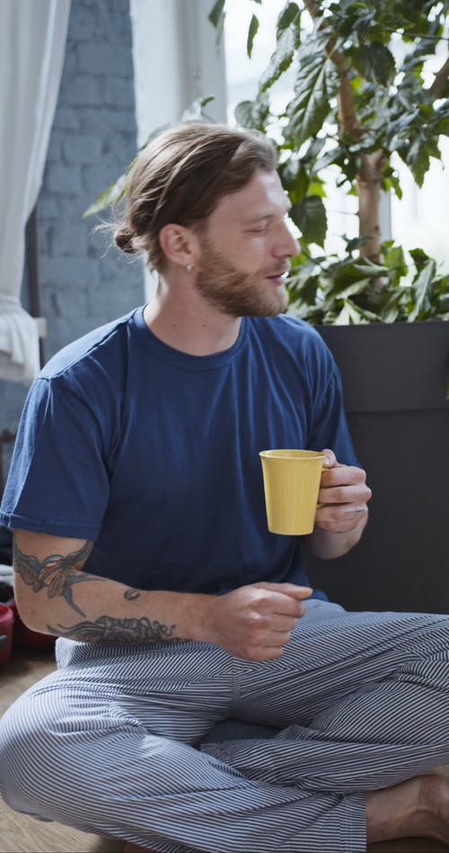 Man Sitting on Floor Near a Houseplant While Dancing