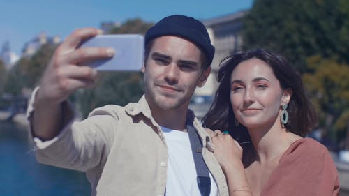 Couple Smiling While Taking Selfie Using a Smartphone