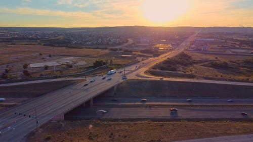 Drone Footage of Vehicles Driving on Expressway During Golden Hour