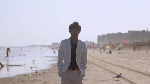 A Man In A Formal Wear Walking In The Beach