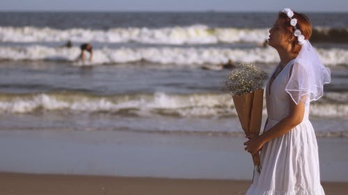 Bride with a Bouquet of Flowers at the Beach