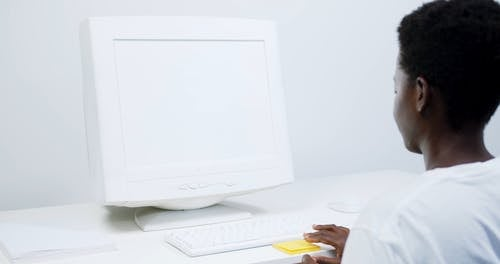 Boy Placing Sticking Notes on PC Monitor