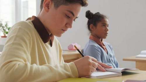 A Young Male Student Writing On His Notebook
